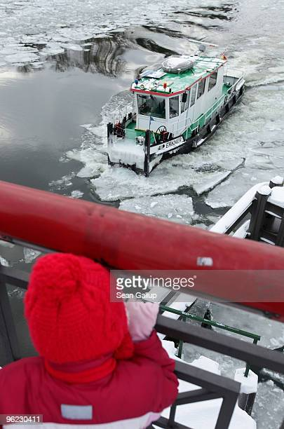 A child watches an icebreaker churn through ice in the Dahme river in the district of Koepenick on January 28 2010 in Berlin Germany Though...