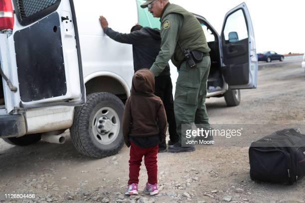 A child watches as a US Border Patrol agent searches a fellow Central American immigrant after they crossed the border from Mexico on February 01...