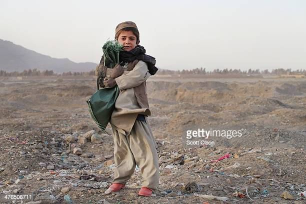 A child watches as soldiers with the US Army's 4th squadron 2nd Cavalry Regiment patrol through his village on March 3 2014 near Kandahar Afghanistan...