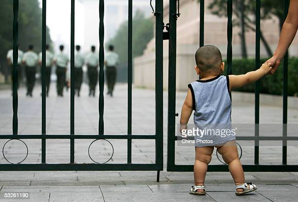A child watches military soldiers who guard the Great Hall of the People take part in training July 19 2005 in Beijing China Various of celebrations...