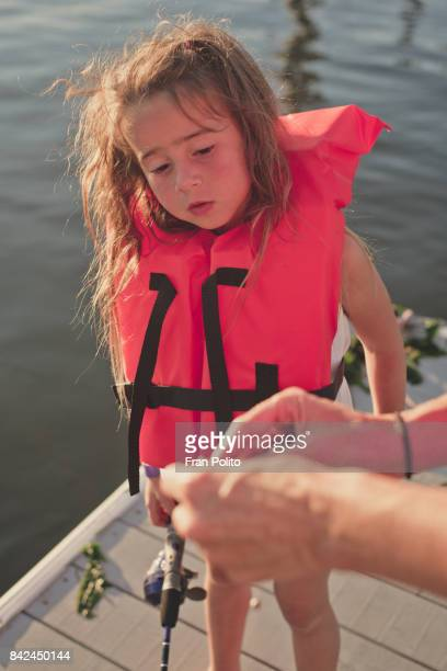 Child watches mother bait fishing hook.