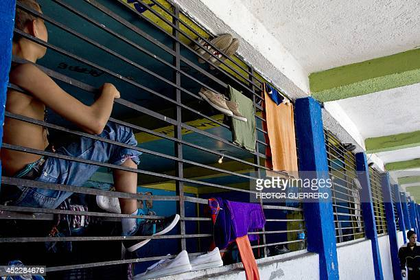 A child watches through a barred window inside La Gran Familia shelter where more than 48 hours ago police rescued 596 people including 458 children...