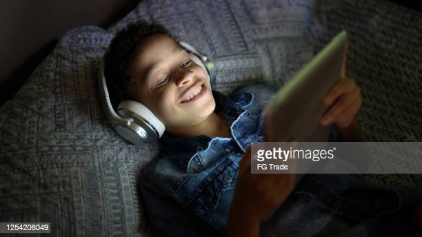 child watching a movie using digital tablet at bed - downloading stock pictures, royalty-free photos & images