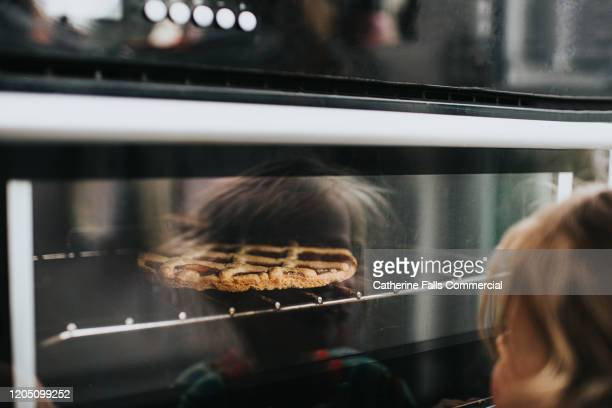 child watching a pie bake in an oven - dessert stock pictures, royalty-free photos & images