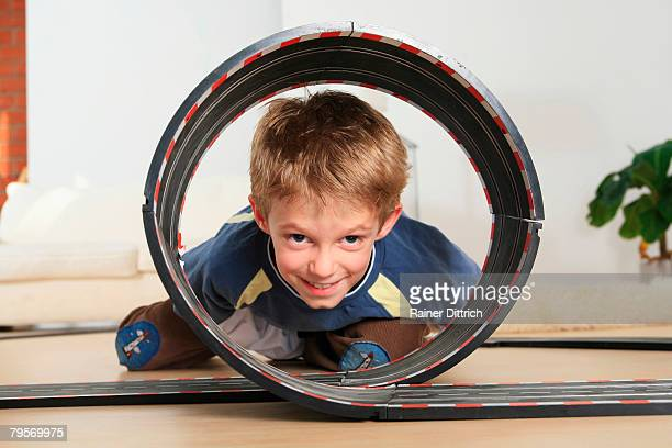 Child (7-9) watching through toy racetrack
