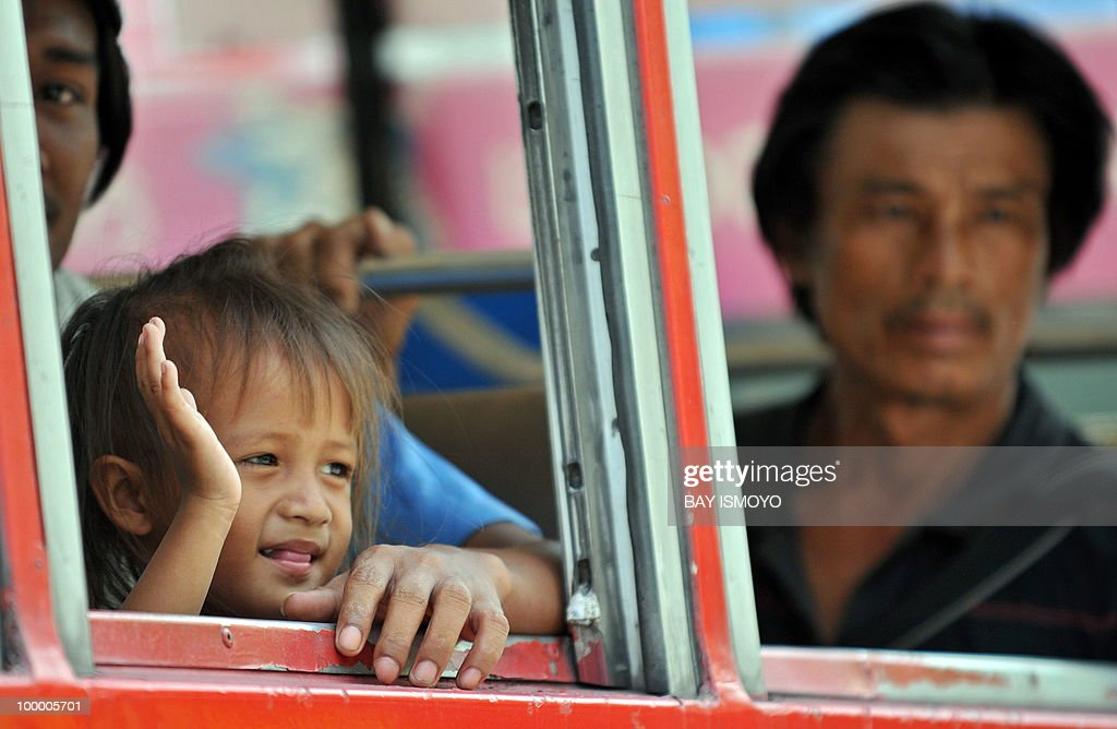 A child waves as 'Red Shirt' anti-government protestors board buses out of their dismantled protest site a day after an army assault, in downtown Bangkok on May 20, 2010. Plumes of smoke hung over the Thai capital and gunfire crackled As troops moved to crush militants who went on the rampage after a deadly crackdown on their anti-government protest camp.