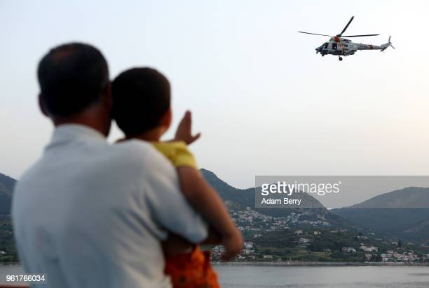 A child waves at a Greek military helicopter flying above the Aegean Sea waters between the island of Lesbos and Turkey on May 23 2018 in Mytilene...
