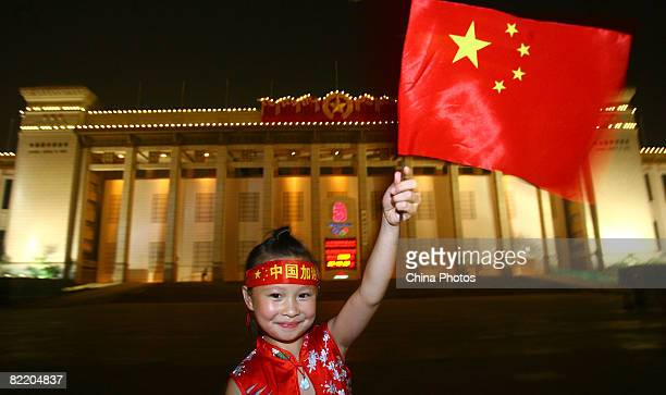 A child waves China's national flag in front of the 2008 Olympics countdown clock at Tiananmen Square on August 7 2008 in Beijing China