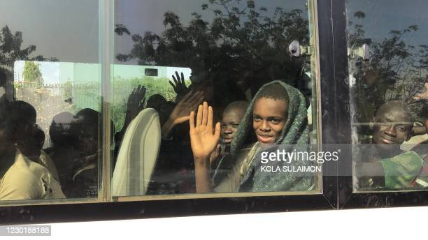 Child waves his hand from within a bus as children kidnapped by Boko Haram from the Government Science Secondary school, in Kankara, in northwestern...