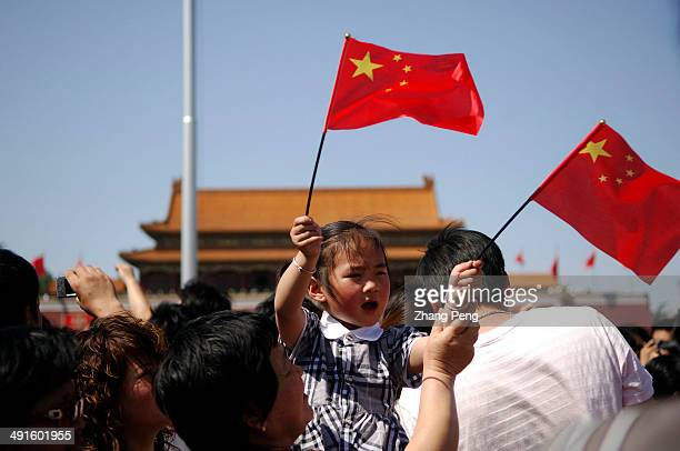 A child waves the national flag as people gather on Tian'anmen Square to commemorate the first anniversary of the Sichuan earthquake that killed...