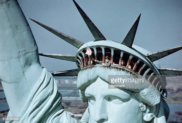 A child waves the United States flag from the crown of Liberty Enlightening the World less formally known as The Statue of Liberty on Liberty Island...