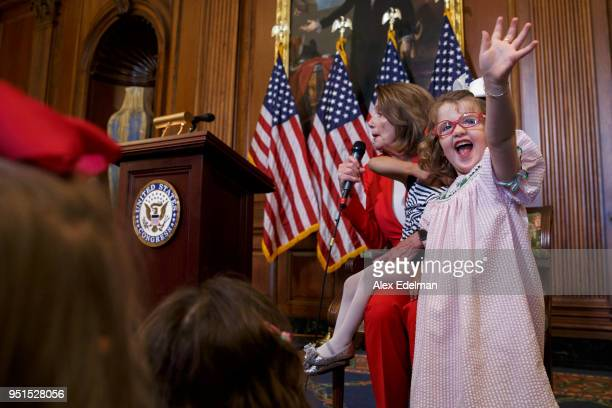 A child waves to her parent as House Minority Leader Nancy Pelosi speaks with journalists' kids during her weekly press conference on 'Take our...