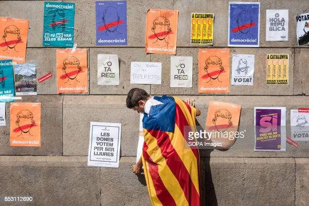 A child wearing a Catalan flag on his back hangs several pro referendum posters on the walls of the University of Barcelona Pro independence...
