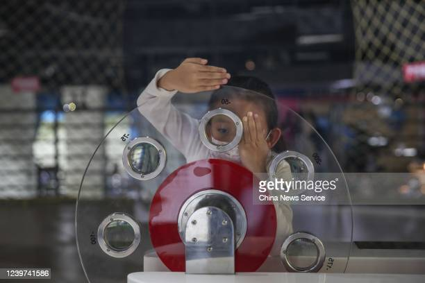 A child wearing a face mask plays with eyesight measuring equipment at Guiyang Science and Technology Museum on International Children's Day on June...
