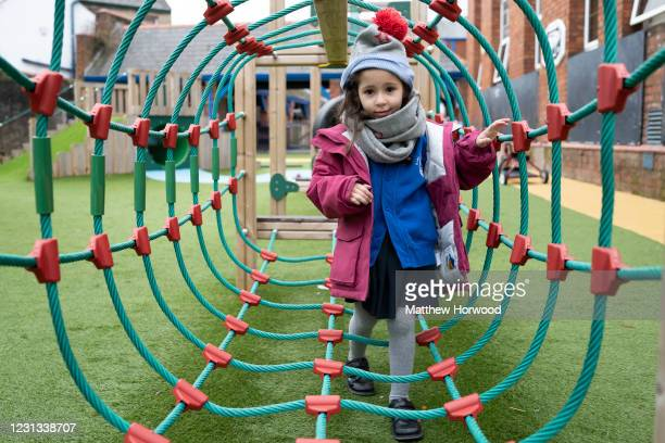 Child wearing a hat and scarf plays outdoors at Roath Park Primary School on February 23, 2021 in Cardiff, Wales. Children aged three to seven began...