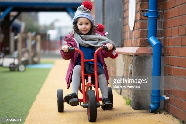 Child wearing a hat and scarf rides a bike at Roath Park Primary School on February 23, 2021 in Cardiff, Wales. Children aged three to seven began a...