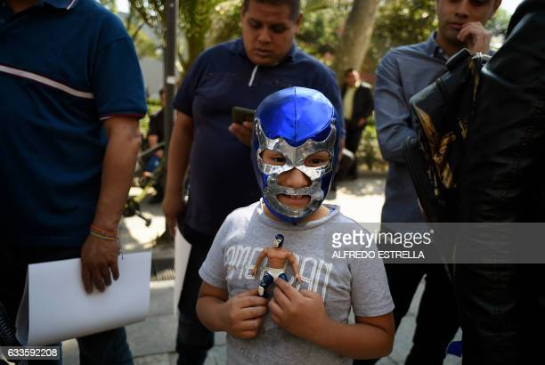 A child wearing a mask of Mexican wrestler Blue Demon Jr waits to have his autograph during a traditional event for Candelaria Day on February 2 2017...