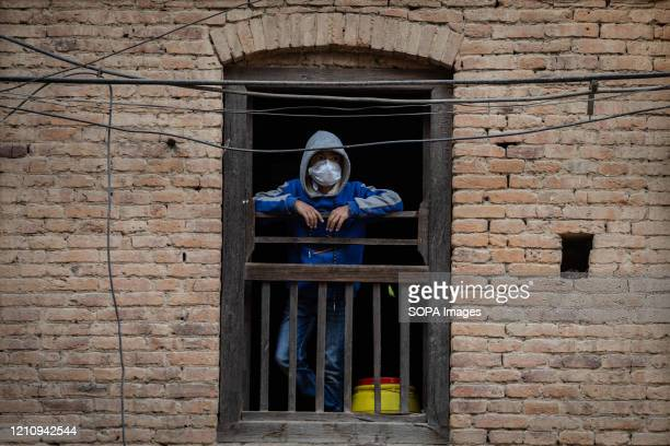A child wearing a medical mask looking outside through a wooden window during the covid 19 confinement It has been a month since the lockdown...