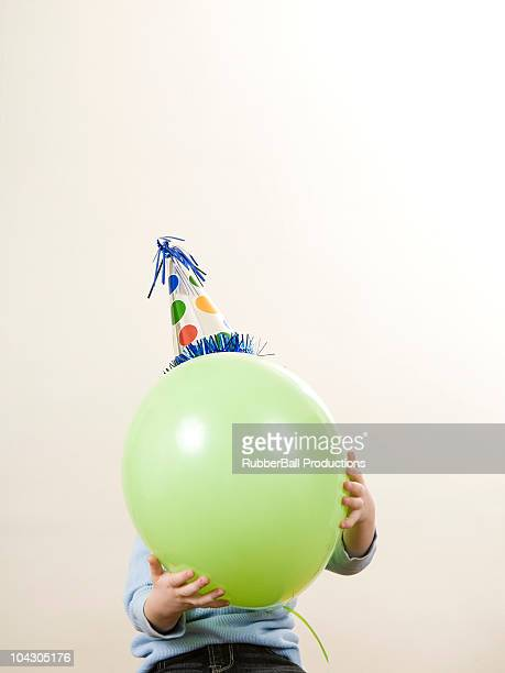 child wearing a party hat holding a balloon in front of his face
