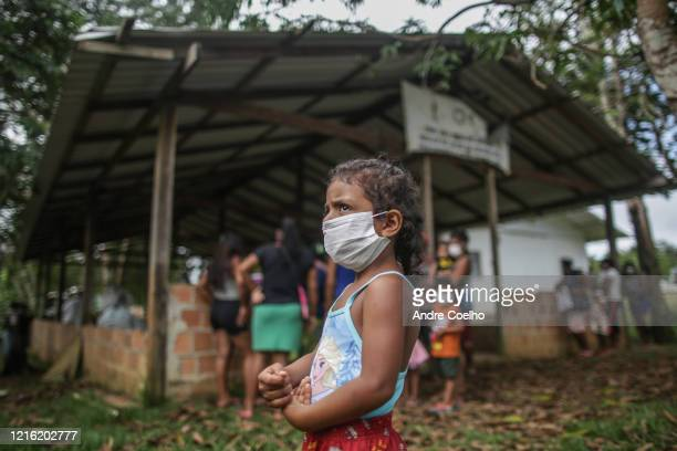 Child wearing a protective mask waits to be vaccinated against flu at the riverside community of Belavista do Jaraqui, in Negro river, about one hour...