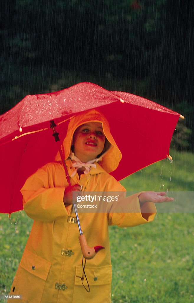 Child wearing a raincoat in the rain : Stockfoto
