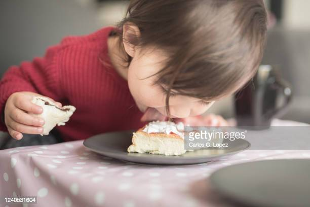 child wearing a red top licks the cream off a cake on a plate - lifestyles photos stock pictures, royalty-free photos & images