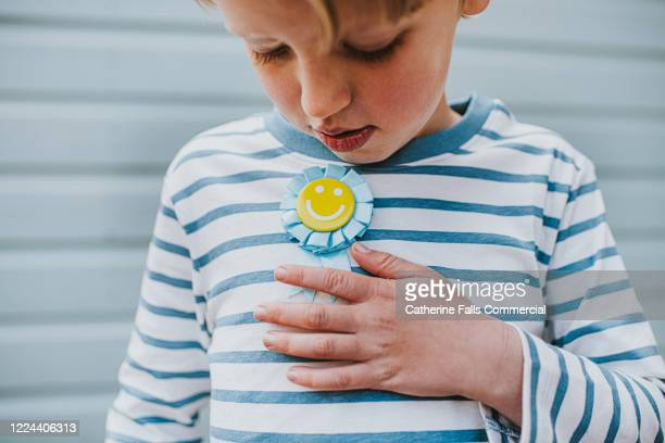 child wearing a rosette - brooch stock pictures, royalty-free photos & images