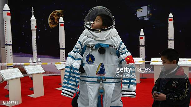 A child wearing a simulated Shenzhou VII space suit poses for photos in front of rocket models at the Wenzhou Spaceflight Exhibition on January 2...