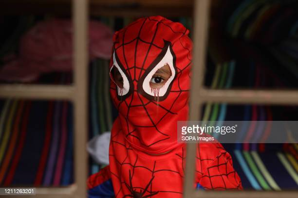 Child wearing a spider-man costume looks out of the window during the lockdown. Around 71% of the children said they feel isolated and lonely due to...