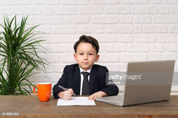 child wearing a suit like a businessman and he work in his office. - formal businesswear stock pictures, royalty-free photos & images