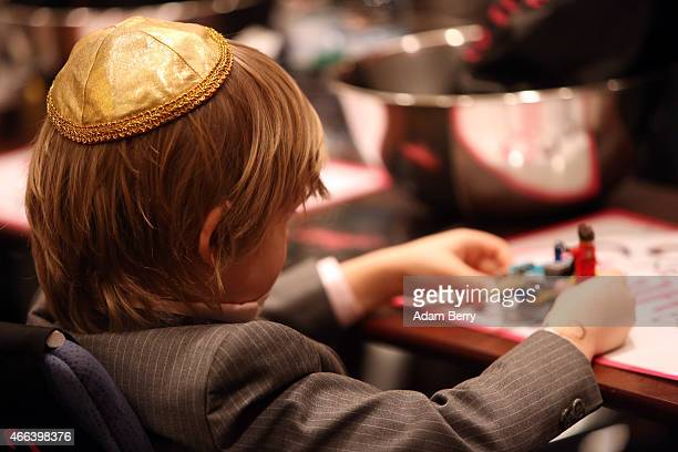 A child wearing a yarmulke plays with legos during the Mega Challah Bake at the local Chabad community's Kosher Festival on March 15 2015 in Berlin...