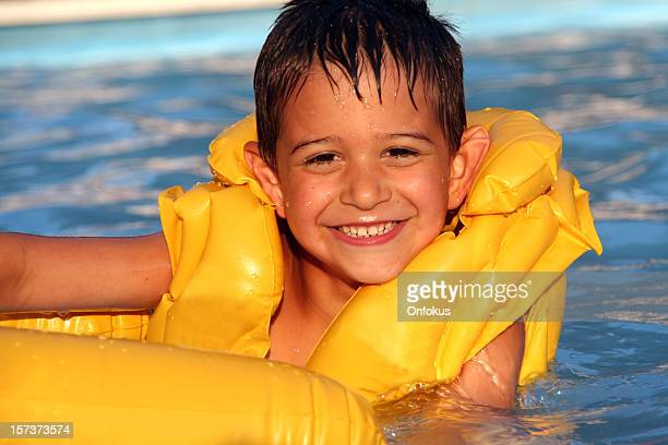 Child Wearing a Yellow Life Jacket in Swimming Pool