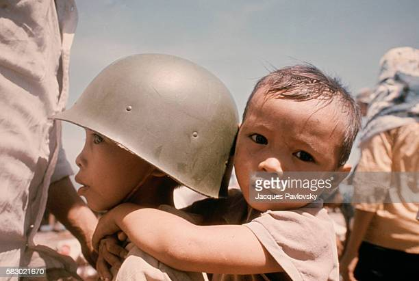 A child wearing an army helmet carries a younger infant on his back. On April 29, 1975, American forces withdrew from Saigon, leaving the noncommunist capital to fall to North Vietnamese tanks.