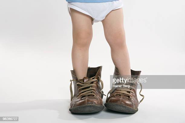 child wearing big shoes, low section - tamanho desproporcionado - fotografias e filmes do acervo