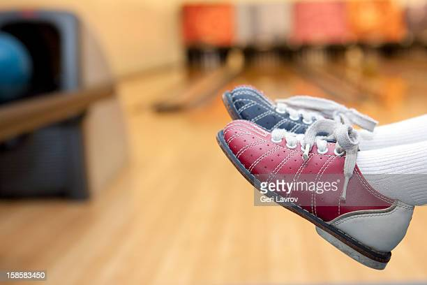 Child wearing bowling shoes at a bowling alley