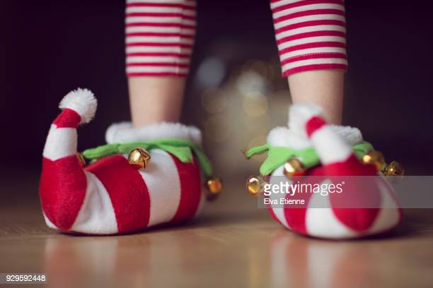 child wearing christmas elf novelty slippers with bells - pixie stock photos and pictures