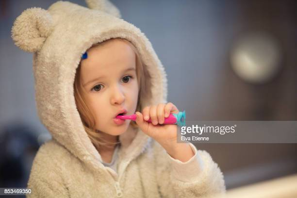 Child(4-5) wearing cozy pyjamas and brushing teeth