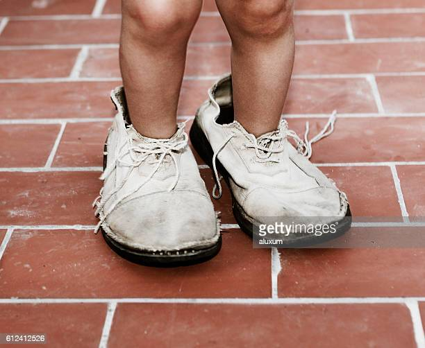 child wearing deteriorated adult shoes - big foot stock photos and pictures