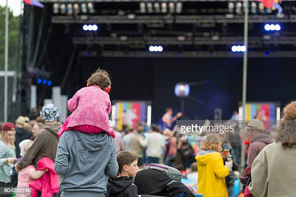 Child wearing ear defenders at a Scottish music festival