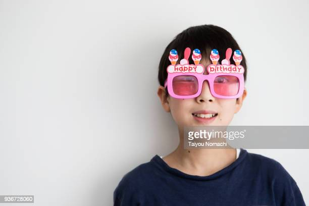 a child wearing eyeglasses for birthday - 男の子一人 ストックフォトと画像