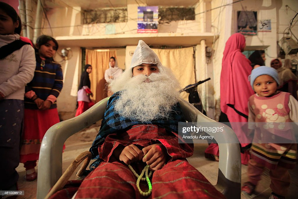 A child wearing false beard sits on a chair as streets and buildings are decorated with lights and ornaments within the ceremony marking the 1444th anniversary of the birthday of Prophet Mohammad, Mawlid al Nabi, in Rawalpindi, Pakistan on January 3, 2015.