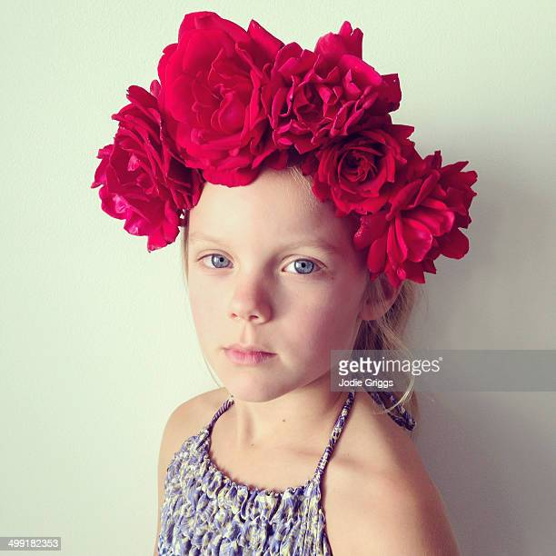 Child wearing flower crown made from red roses