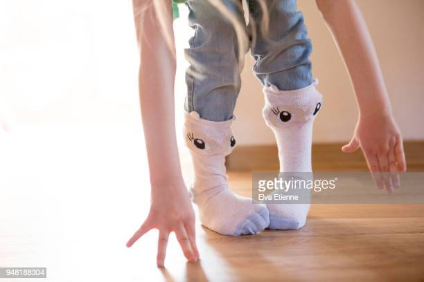 Child wearing funny face socks and losing her balance