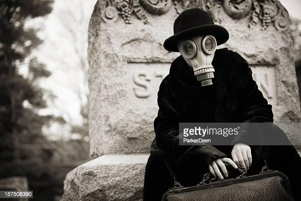 child wearing gas mask in cemetery with vintage doctor bag - dokterstas stockfoto's en -beelden