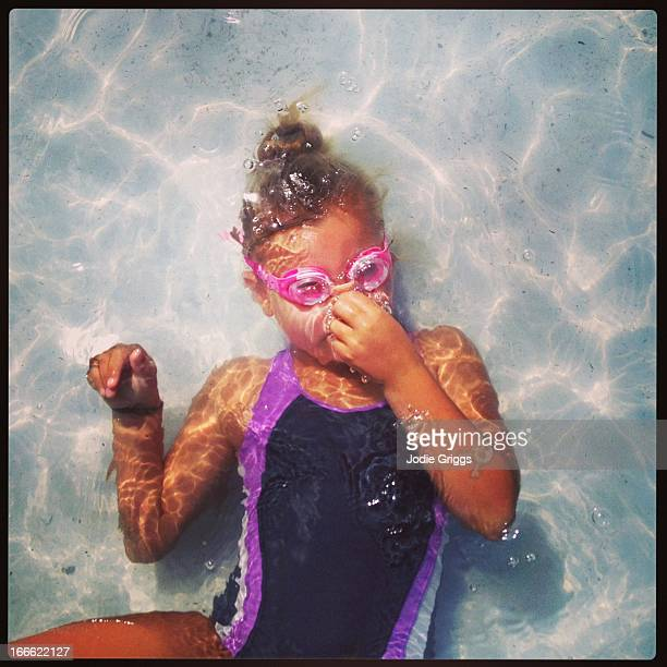 Child wearing goggles swimming underwater in pool