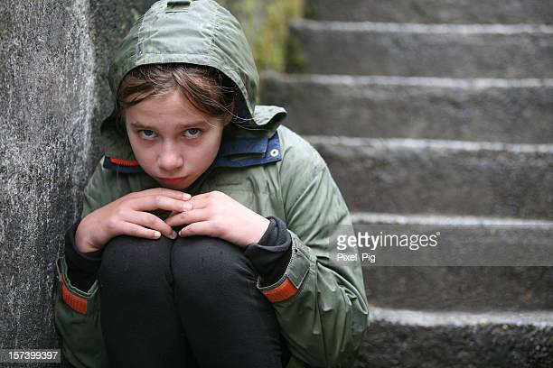 child wearing green coat sitting on stairs - hongerig stockfoto's en -beelden