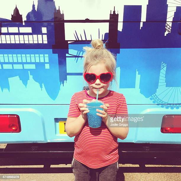 Child wearing heart glasses drinking icy drink