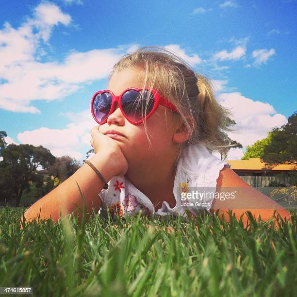 Child wearing heart glasses laying on grass