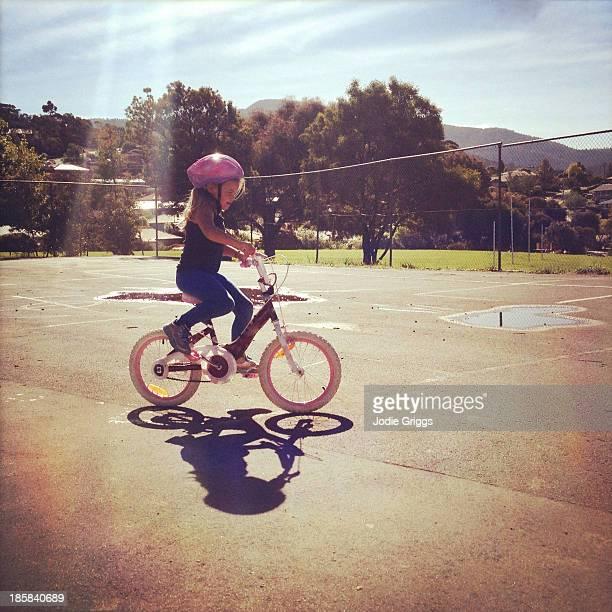 Child wearing helmet riding a bike on summer day