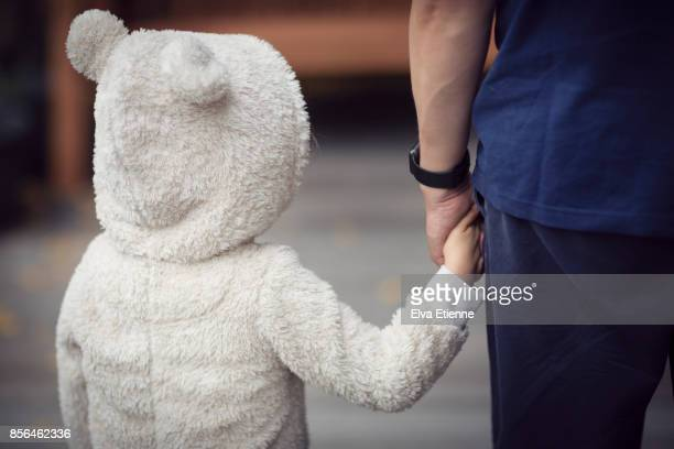 Child wearing hooded bear costume, holding hands with father